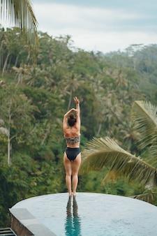 ジャングルの景色を望むスイミングプールの女性