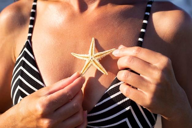 日焼けした体を背景に水着姿の女性がヒトデを抱えている。
