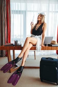 Женщина в купальнике и в ластах сидит на столе в офисе и думает о путешествии.