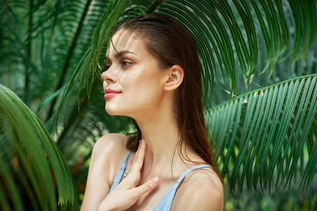 Женщина в купальнике возле зеленых листьев в экзотических джунглях