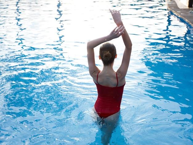 水着姿の女性が手を上げてプールの青い水に立つ