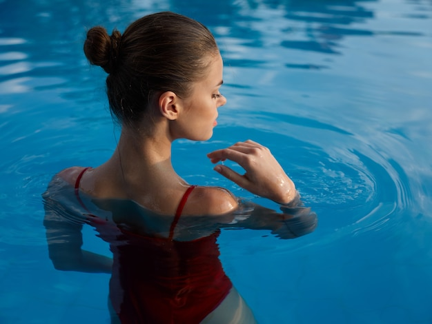 プールで泳いでいる水着の女性贅沢な休暇の背面図