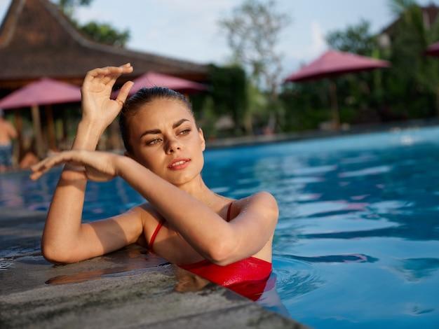 プール熱帯島の贅沢で泳ぐ水着の女性
