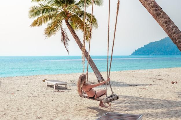 Женщина в купальнике качается на качелях у океана под пальмами, отдых на море и путешествия.