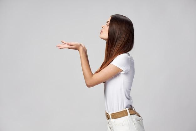 Женщина в футболке и шортах посылает воздушный поцелуй