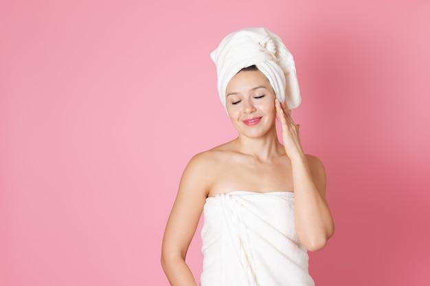 タオルを着た女性は、スパケアや顔の弾力性のある水分補給を楽しんでいます