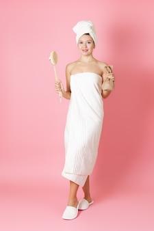 タオルの上の女性は、アンチセルライトマッサージとスクラブのための木製のブラシを保持しています