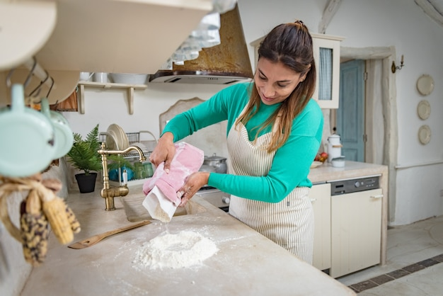 Женщина на традиционной винтажной кухне замешивает тесто для домашнего хлеба
