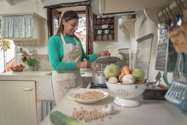 Женщина на традиционной винтажной кухне готовит еду из старых горшков и овощей