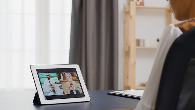 Женщина в видеозвонке на планшетном компьютере из домашнего офиса.