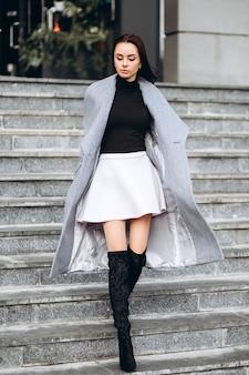 Женщина в теплом пальто и белой юбке на открытом воздухе