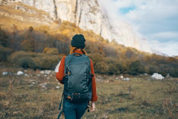 彼女の背中にバックパックと山の屋外のセーターで暖かい帽子をかぶった女性