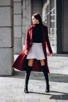 Женщина в теплом красном пальто на открытом воздухе