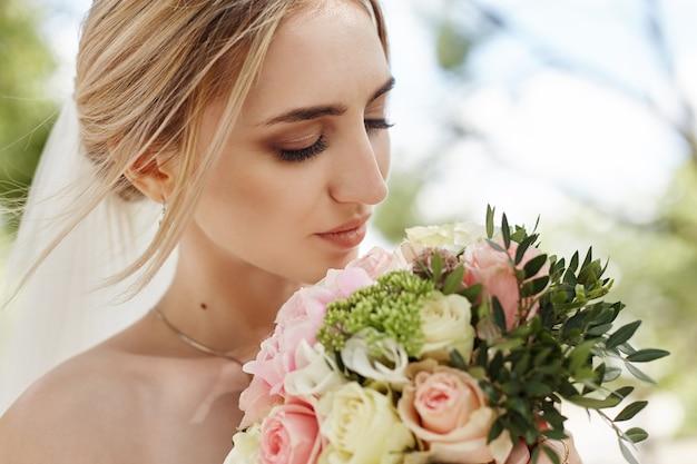 Женщина в свадебном платье держит в руках букет цветов