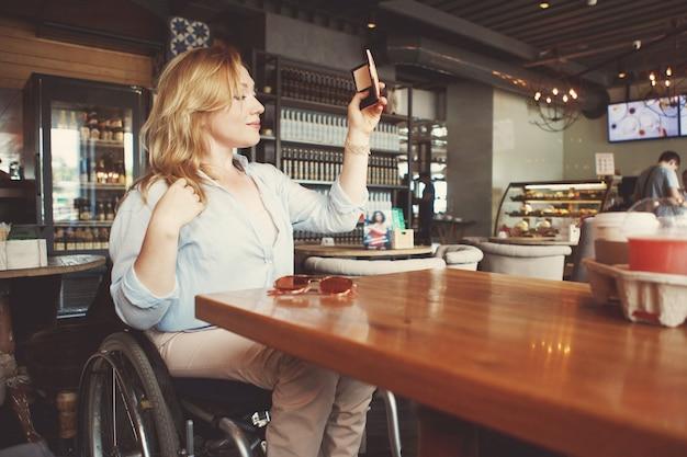 車椅子の女性がカフェのスマートフォンでコーヒーを飲みながら自分撮りをしています。