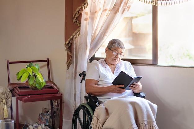 휠체어에 앉아 책을 읽는 여성