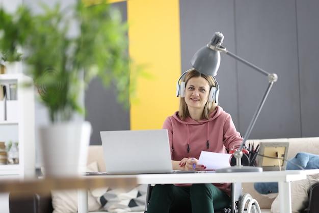 車椅子の女性がヘッドホンをつけて仕事机に座っています。障害を持つ人々のためのリモートワークの概念