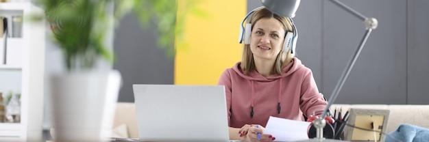車椅子の女性は、ヘッドフォンを付けて仕事机に座っています。障害者のリモートワークのコンセプト