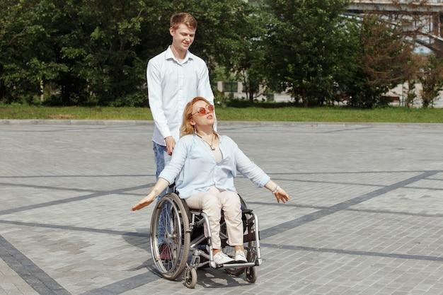 도시 여름 공원에서 산책하는 그녀의 남자 친구와 휠체어에 여자.