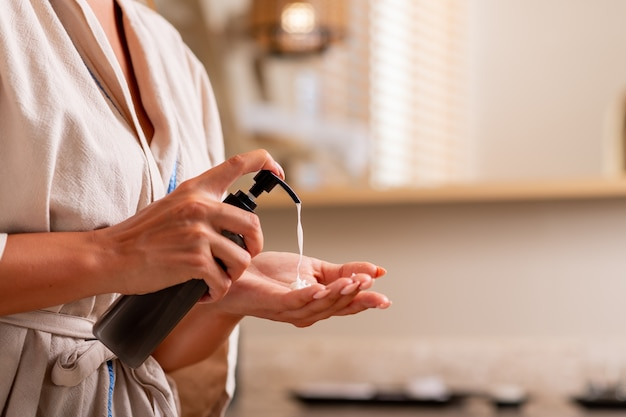 Женщина в белом халате позирует, выжимая масло из бутылки на руке.
