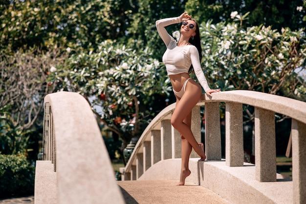 リゾートホテルの近くの橋の上の白いビキニと長袖のポーズの女性。熱帯の国への旅行