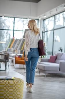 白いブラウスとジーンズを着た女性。ホールから歩いて行くと、後ろから眺めたバーガンディのバッグが見えます。
