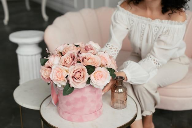 白いブラウスの女性はピンクのソファに座って、ピンクのボックスでピンクの花に触れます
