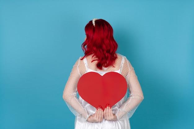 Женщина в белом платье и с рыжими волосами держит за спиной большое красное бумажное сердце, пряча лицо