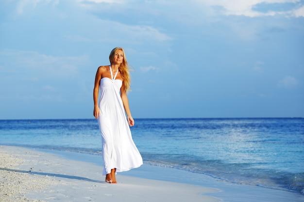 海の海岸で白いドレスを着た女性