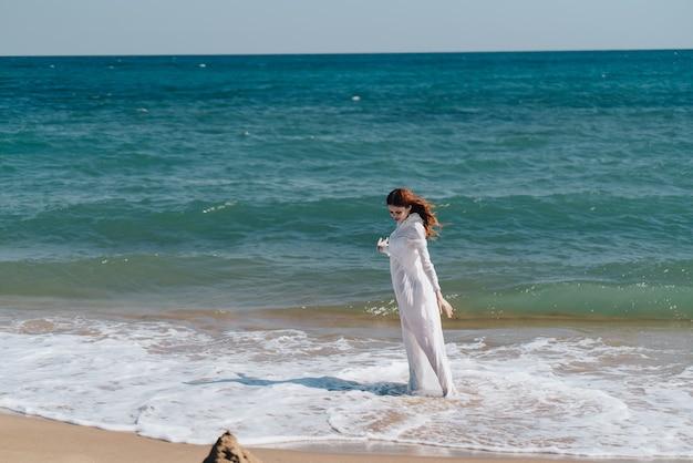 Женщина в белом платье, стоя на пляже