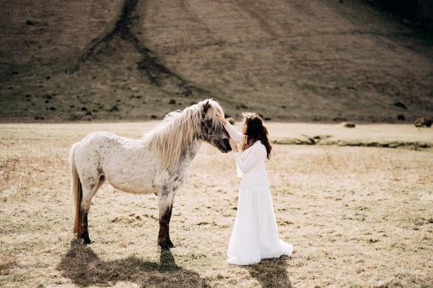 白いドレスを着た女性が白い馬の顔を撫でます。アイスランド