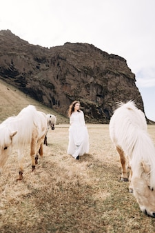 白いドレスを着た女性は、シックなたてがみを持つクリーム色の馬の間でフィールドを横切って歩きます