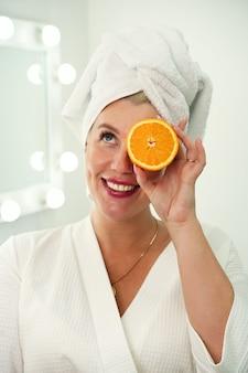 バスルームの白いローブを着た女性は、オレンジの半分を手に持っています。スキンケアビタミンf ...