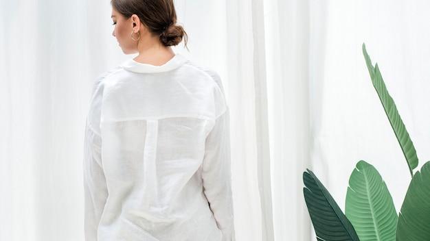 Strelitzia 식물 옆에 서 있는 흰 셔츠를 입은 여자