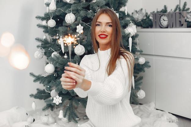 Женщина в белом свитере сидит у елки