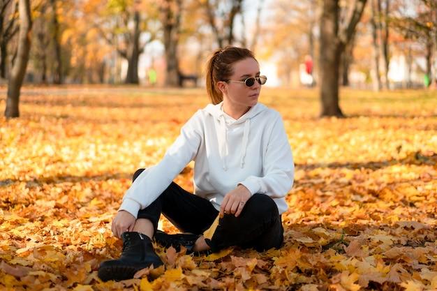 フード付きの白いセーターを着た女性が公園の地面に座って、手に葉を持っています。