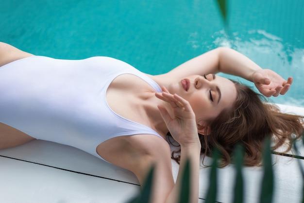 スイミングプールのそばの白い水着の女性。