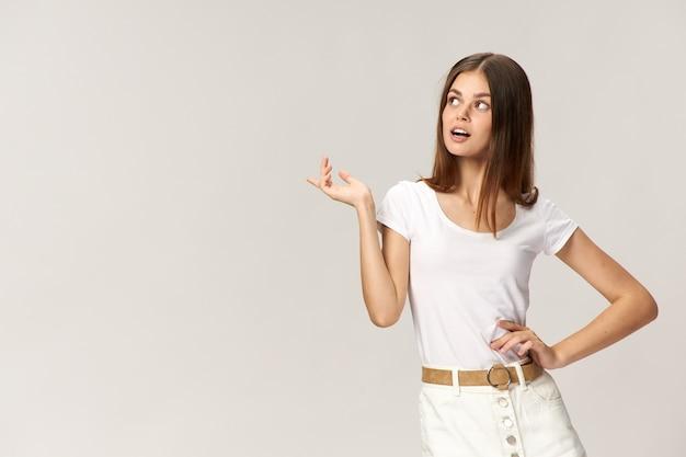 白いtシャツを着た女性が腰に手をかざし、横に指を見せます