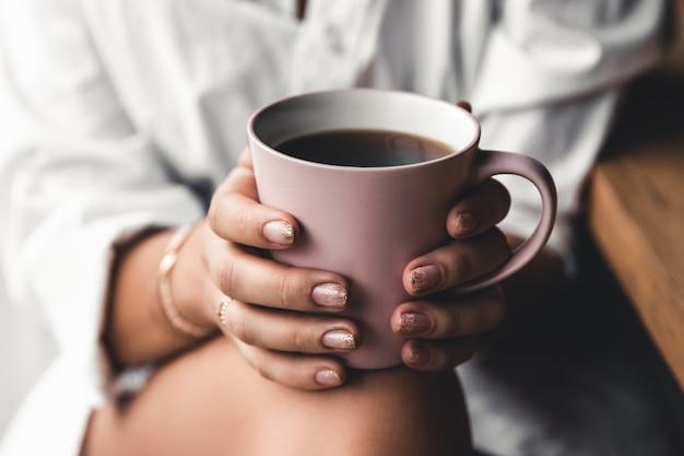 白いtシャツを着た女性は、ピンクのセラミックカップで朝のコーヒーを保持しています。マニキュア。正面図