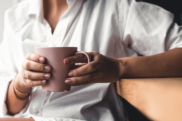 Женщина в белой футболке держит утренний кофе в розовой керамической чашке. маникюр. передний план