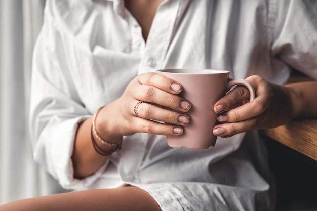 흰색 티셔츠를 입은 여성이 분홍색 세라믹 컵에 모닝 커피를 들고 있습니다. 매니큐어. 전면보기