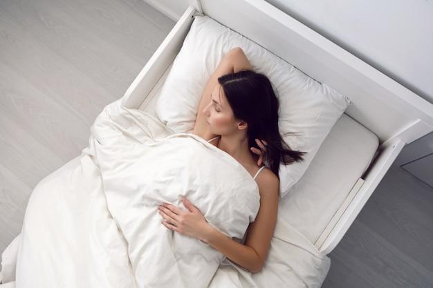 흰색 티셔츠를 입은 여자가 침대에 누워 있고 베개가 방의 담요 아래에 있습니다.