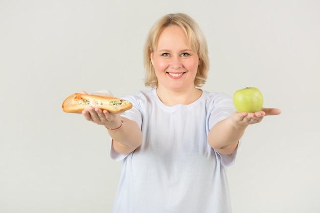 サンドイッチとリンゴと白いtシャツの女性