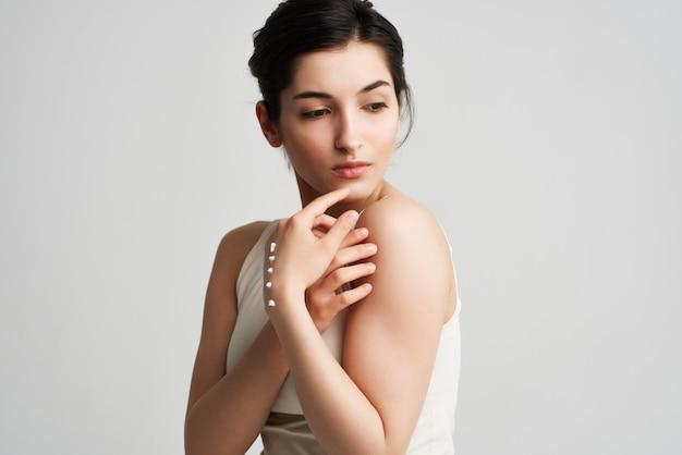 그녀의 손에 흰색 티셔츠 크림을 입은 여성 건강한 피부 밝은 배경