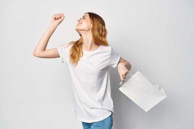 Женщина в белой футболке с пакетом в руках на светлом фоне покупок подарков