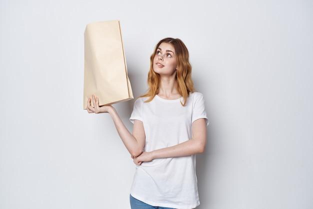 그녀의 손에 쇼핑 패키지와 함께 흰색 티셔츠에 여자