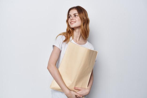 彼女の手で買い物をするパッケージを持つ白いtシャツの女性