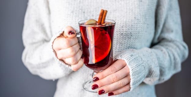 그녀의 손에 mulled 와인 한 잔을 들고 흰색 따뜻한 스웨터에 여자