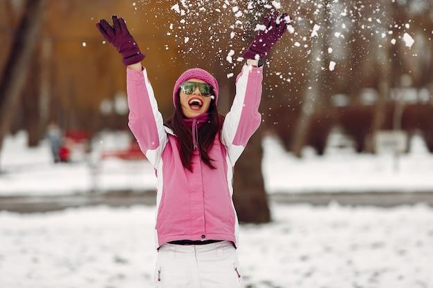 冬の公園の女性。ピンクのスポーツスーツの女性。サングラスをかけた女の子。