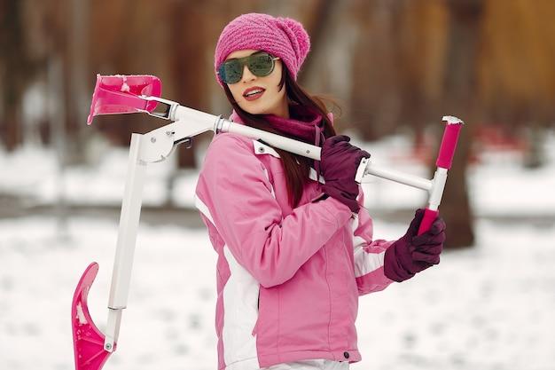冬の公園の女性。ピンクのスポーツスーツの女性。スノースクーターを持つ女性。